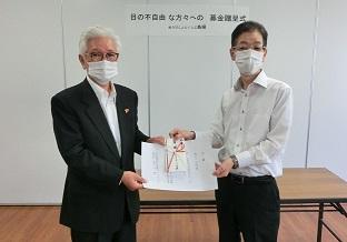 贈呈の様子を写した写真 ぬうびじょんくらぶ島根の宇田川会長(左)と寄贈を受ける青戸理事長(右)